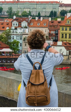 THE CZECH REPUBLIC, PRAGUE - MAY 19: Woman is taking pictures on the Charles bridge in Prague, Czech on May 19, 2015 - stock photo