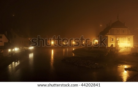The Czech town Krumlov covered in fog by night - stock photo