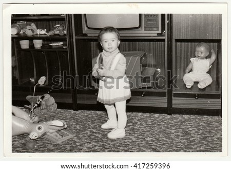 THE CZECHOSLOVAK SOCIALIST REPUBLIC - CIRCA 1970s: Retro photo shows child (girl) who plays with toy. Black & white vintage photography.