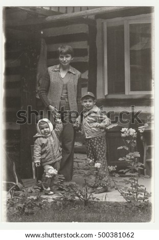 THE CZECHOSLOVAK  SOCIALIST REPUBLIC - CIRCA 1980s: Vintage photo shows an adolescent  girl with two children. They pose in front of log cabin. Retro black & white  photography.