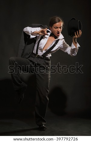The dancing girl with cigar in a men's suit and tie butterfly, against dark background. (rigid light and shadows)