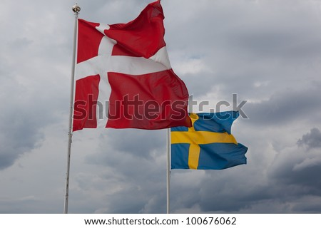 The Danish and Swedish flag waving in the wind - stock photo