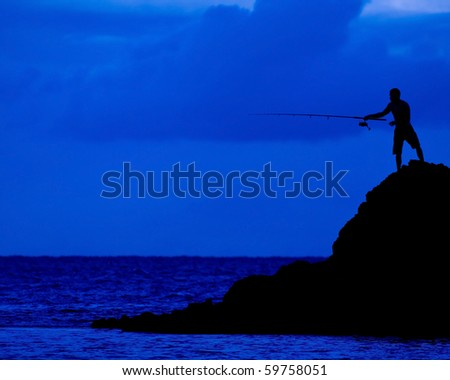 The dark figure of a man fishing from a rock into the sea