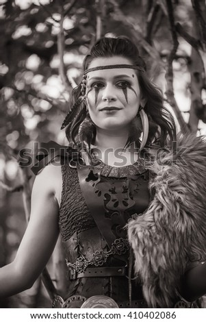 The dark-haired warrior in armor Amazon in forrest. Black and white - stock photo