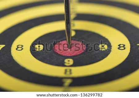 the dart hitting the middle of dartboard, close up