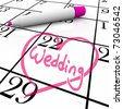 The date of a wedding is circled on a white calendar with a magenta colored marker, surrounded by a drawn heart - stock photo