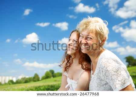 The daughter and elderly mother against the sky and park - stock photo