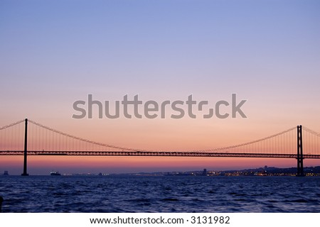 The 25 de Abril Bridge   is a suspension bridge connecting the city of Lisbon, capital of Portugal, to the municipality of Almada on the left bank of the Tagus river. I - stock photo