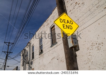 "The ""Dead End"" road sign with building in background."