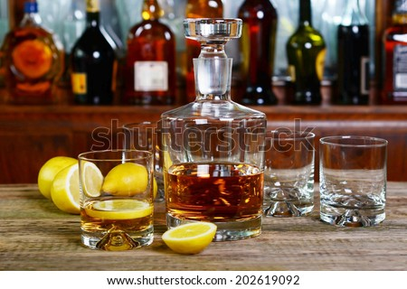 The decanter of whiskey and two empty glasses - stock photo