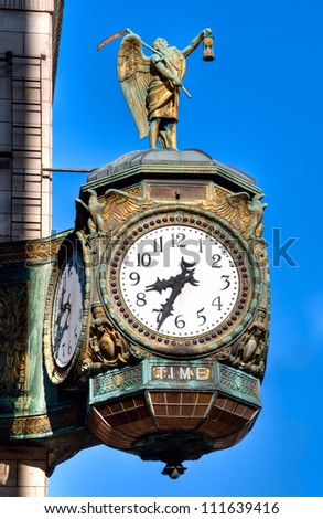The 1926 decorative jewelers' building clock in Chicago is emblazoned with the word TIME and decorated with a statue of old Father Time. - stock photo