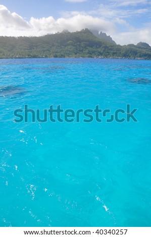 The deep blue waters of the lagoon in Tahiti. - stock photo