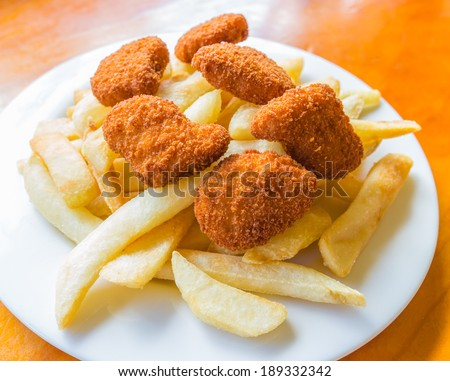 The deep fried potato chips and chicken nuggets on the white dish with the wooden table