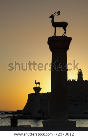 The deer statues at the entrance to  Rhodes harbor at sunrise - stock photo
