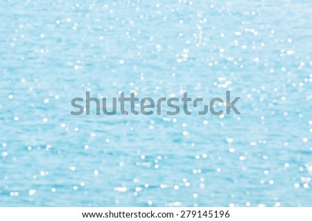 The Defocused Of Water surface with waves glittering in the sun. Out of focus bokeh of sun glares reflected - stock photo