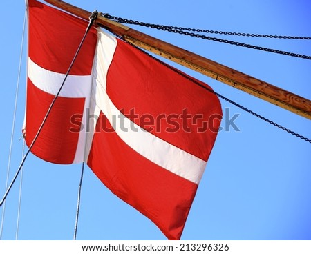 The denmark or danish flag on sailboat with blue sky on background - stock photo