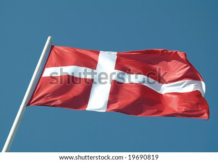 The denmark or danish flag waving on blue sky - stock photo