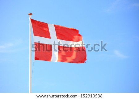The denmark or danish flag with blue sky on background - stock photo