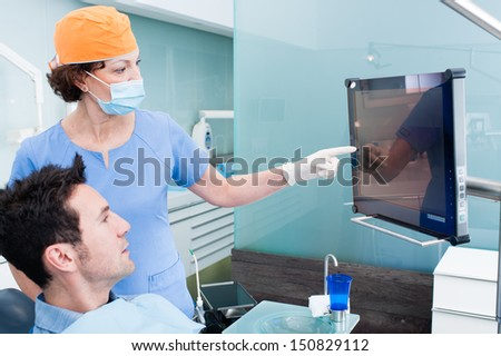 The dentist and the patient commenting about medical treatment - stock photo