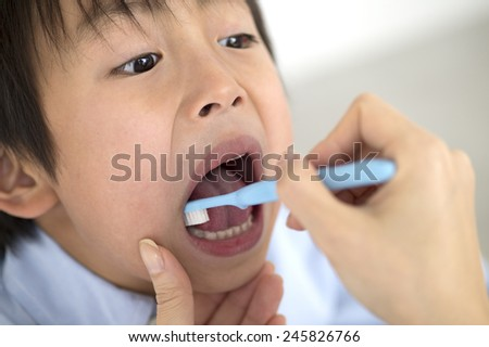 The dentist polishing boy's tooth - stock photo