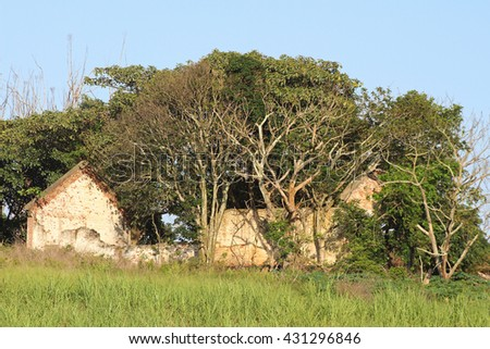 The derelict ruin of a wrecked, old farmhouse in a field in rural Africa. - stock photo
