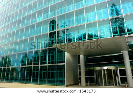 The deserted front door of a large commercial office block, surrounded by trees reflected in the glass. One tree reflection appears to grow out of a pillar of the entrance. - stock photo