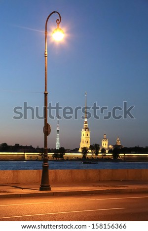 The deserted street illuminated by a lone lamppost - stock photo