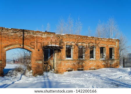 The destroyed building against the blue sky - stock photo