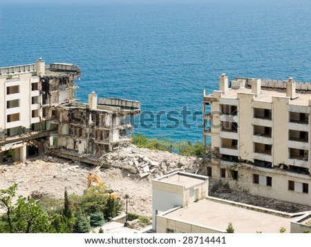 The destroyed buildings on seacoast. Consequences of earthquake - stock photo