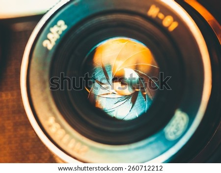 The diaphragm of a camera lens aperture. Selective focus with shallow depth of field. Color toned image. - stock photo