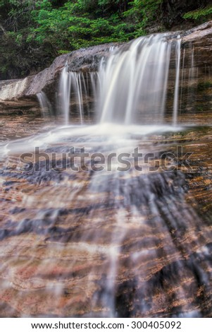 The diminutive  Elliot Falls spills over and cascades down the sandstone shoreline of Lake Superior's Pictured Rocks National Lakeshore in Upper Peninsula Michigan. - stock photo