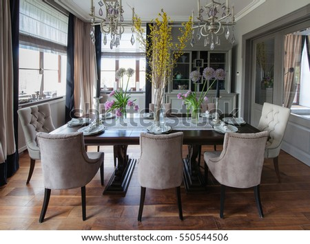 The dining room in shades of olive with a wooden table.