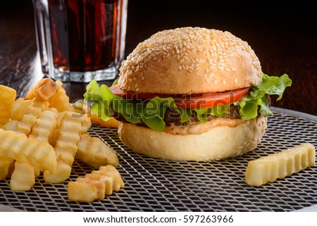 The dinner is served. This picture could make you hungry: a tasty burger with beef and vegetables, french fries scattered over a gridded silver tray and a glass of cola to wash it all down.