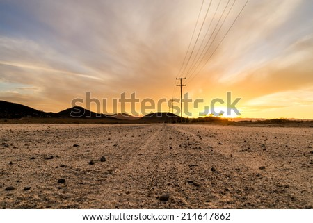 The dirt road on a beautiful Southern California sunset. - stock photo