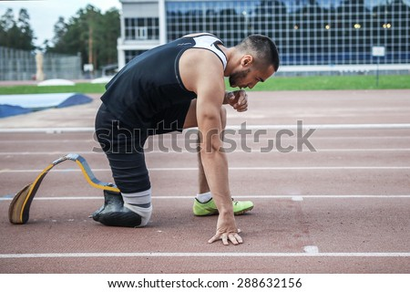 The disabled athlete preparing to start running - stock photo