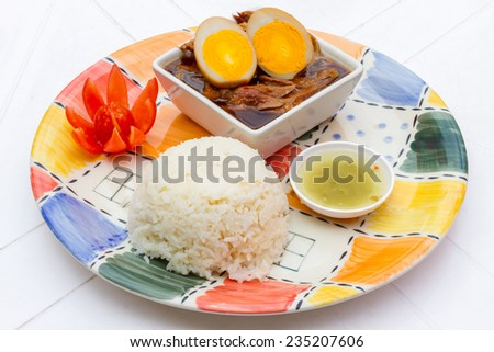 The dish of Stewed pork leg on steam rice and sauce, tradional thai food, stewed pork leg with boiled egg and preserve (Kao Ka Moo)  - stock photo
