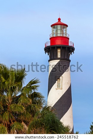 The distinctive St. Augustine, Florida Lighthouse stands tall over foreground palm trees in warm late evening light. - stock photo