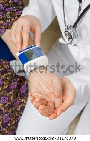 The doctor measure the old woman's blood pressure - stock photo
