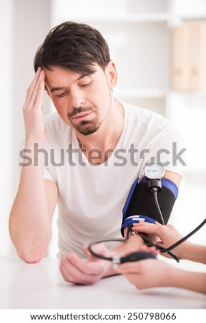 The doctor measures the pressure to young man with headache. - stock photo
