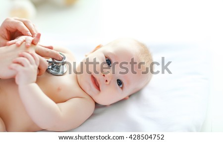 the Doctor pediatrician stethoscope listening to baby - stock photo