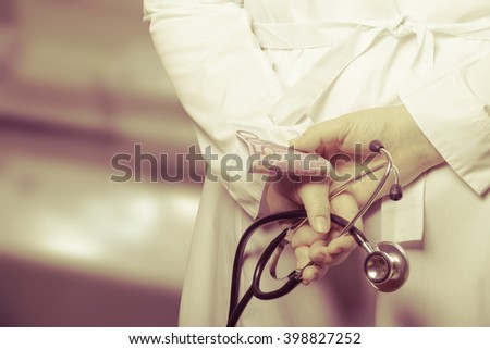 The doctor put his hands with stethoscope and money behind his back on a blurred background. Toned.