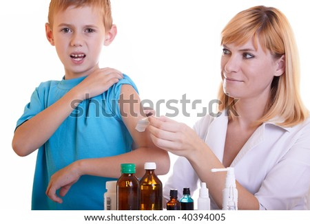 The doctor tears off a plaster by hand the boy - stock photo