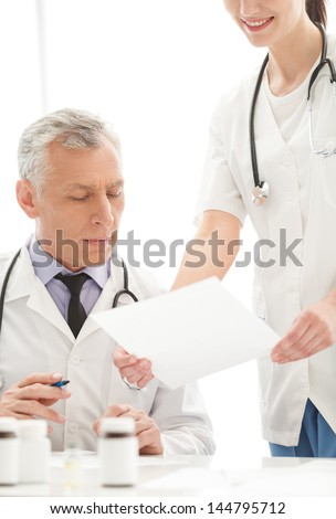 The document to sign. Young cheerful female doctor holding a document to sign while standing near her mature colleague
