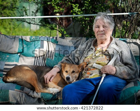 The dog and the old woman in the village, relaxing at their summer cottage. Gray old woman with a stick. Hugs dog