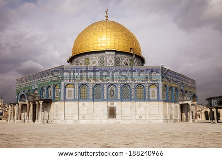 The Dome of the Rock is an Islamic shrine located on the Temple Mount in the Old City of Jerusalem. On this day, sunlight was reflecting from the dome with dark storm clouds behind. - stock photo