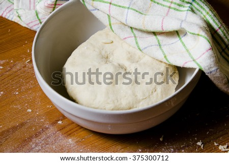 The dough in the bowl under a towel. Preparations for baking the dough in a rustic style.