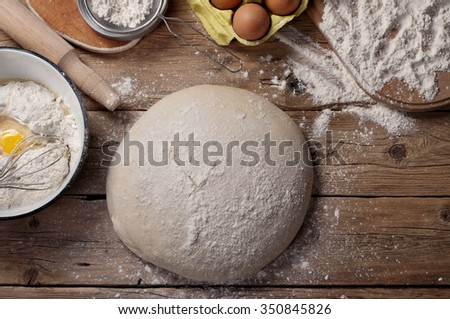 The dough in the form of a loaf of bread on a wooden table in a bakery. Top view. Raw loaf of bread - stock photo
