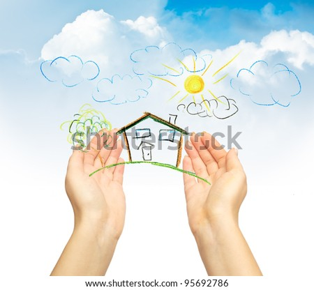 The drawing house in human hands - stock photo