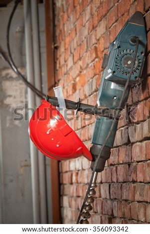 The drill and the red helmet of the Builder weigh on a brick wall - stock photo