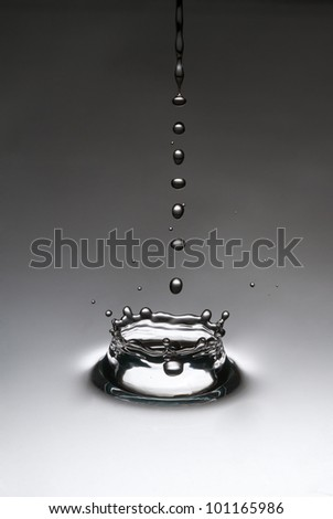 The drop, which falls into the water - stock photo